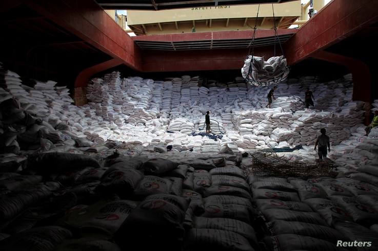Workers unload sacks of rice from a Vietnam cargo ship carrying some 12, 700 tonnes of rice, at the port in Manila July 5, 2014.