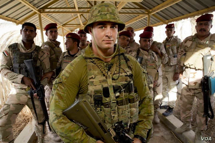 Australian Army soldier Private Dennis Lee stands with soldiers from the Iraqi Army while providing force protection at the Taji Military Complex, Iraq.