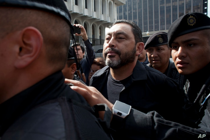 FILE - Guatemala's former Interior Minister, Mauricio Lopez Bonilla, is escorted by police as he arrives to a court in Guatemala City, June 11, 2016.