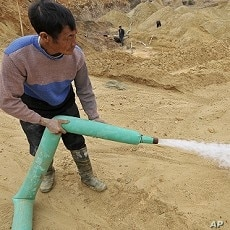 A Chinese worker waters the site of a rare earth metals mine at Nancheng county, Jiangxi province, December 29, 2010.