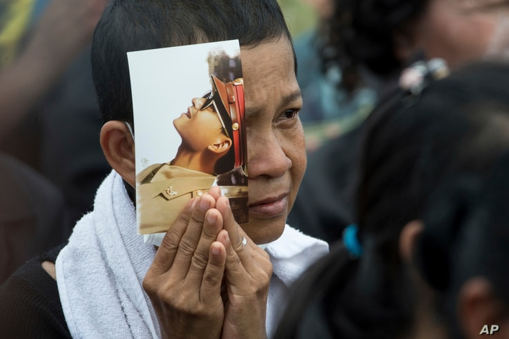 A mourner holds a portrait of the late King Bhumibol Adulyadej during his funeral procession and royal cremation ceremony in Bangkok, Thailand, Oct. 26, 2017.