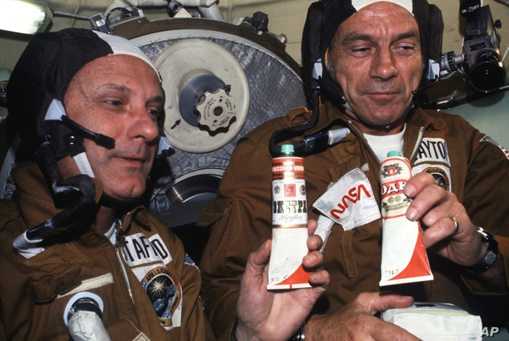 """1975: Astronauts Thomas P. Stafford (left) and Donald K. """"Deke"""" Slayton hold containers of Soviet space food in the Soyuz Orbital Module during the joint U.S.-USSR Apollo-Soyuz Test Project docking in Earth orbit mission. The containers hold borsch (..."""