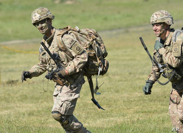 Commander of the 82nd Airborne Division General Richard D. Clarke, left, runs after jumping during a multi-national jump conducted by forces from the U.S., Great Britain and Poland on to a designated drop zone near Torun, Poland, Tuesday, June 7, 201...