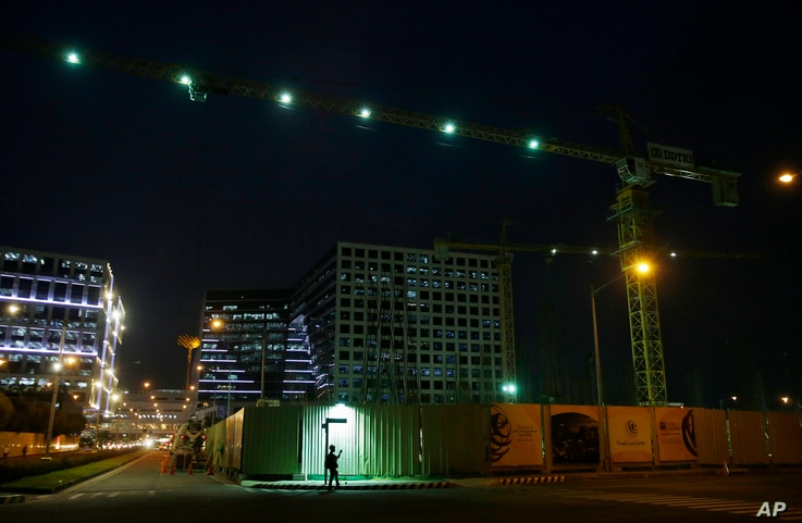 A Filipino worker checks his phone as he waits outside a construction site at a commercial area in suburban Pasay, south of Manila, Philippines, May 19, 2016. The Philippine economy grew faster than expected at 6.9 percent in the first quarter from t...