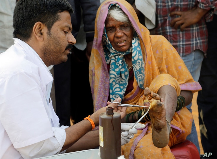 A doctor cleans the wound of a woman farmer at the end of her six day long march on foot, in Mumbai, India, March 12, 2018.