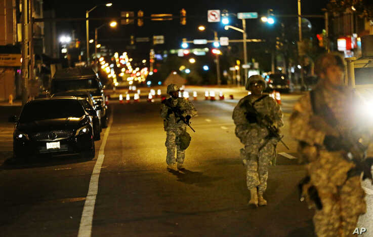 Members of the National Guard walk along North Avenue in Baltimore near where Monday's riots occurred following the funeral for Freddie Gray, after a 10 p.m. curfew went into effect Wednesday, April 29, 2015.