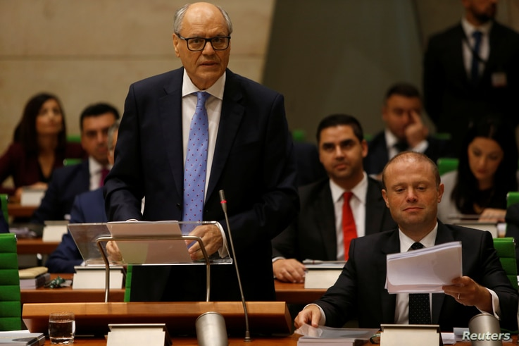 Maltese Finance Minister Edward Scicluna, flanked by Prime Minister Joseph Muscat, presents his government's 2019 budget at parliament in Valletta, Malta, Oct. 22, 2018.