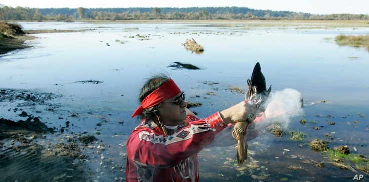 """FILE - Bob Sison, a Nisqually Tribal Elder, burns sage in a """"Welcoming of the Tides"""" ceremony Oct. 31, 2006 near Nisqually, Wash."""