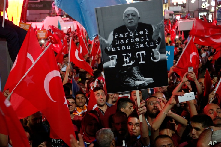 """Supporters of Turkish President Recep Tayyip Erdogan wave their national flags and hold a portrait of Fethullah Gulen, a U.S.-based Muslim cleric, with Turkish words that read: """"the Coup nation traitor, FETO"""" (Feto is the nickname of Fethullah Gulen)..."""