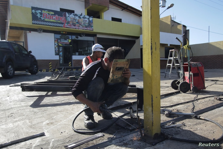 Workers repair the fence of a supermarket, after it was looted in Puerto Ordaz, Venezuela, Jan. 9, 2018.