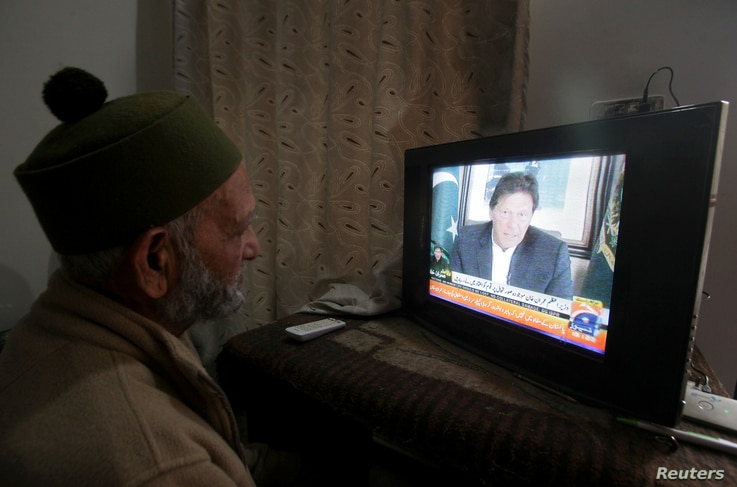 A man watches the speech of the Pakistani Prime Minister Imran Khan, after Pakistan shot down two Indian planes, in Lahore, Pakistan, Feb. 27, 2019.