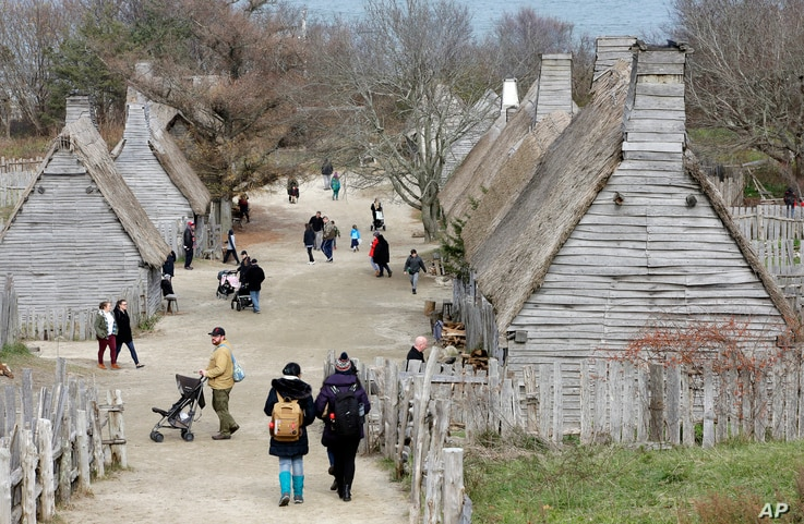 In this Nov. 18, 2018, photo, visitors to Plimoth Plantation, a living history museum village where visitors can get a glimpse into the world of the 1627 Pilgrim village, walk among buildings, in Plymouth, Mass. Plymouth.
