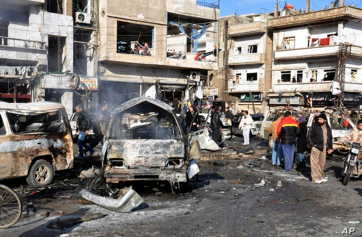 Syrian citizens gather at the scene where twin bombs exploded at a government-run security checkpoint, at the neighborhood of Zahraa, in Homs province, Syria, Jan 26, 2016.