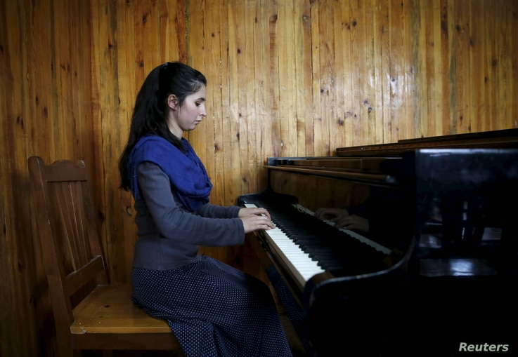 Negin Ekhpulwak, leader of the Zohra orchestra, an ensemble of 35 women, practises on a piano at Afghanistan's National Institute of Music, in Kabul, Afghanistan, April 9, 2016.