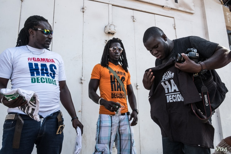 """In exile since 2007, Sheriff Bojang Junior (far right) buys a """"#Gambia Has Decided"""" t-shirt hours after he returns home after former president Yahya Jammeh agreed to relinquish power to Adama Barrow, who won elections in December."""