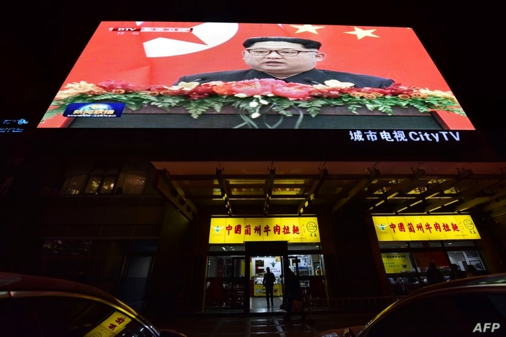 News video footage of North Korean leader Kim Jong Un during his meeting with China's President Xi Jinping is seen on a large screen above a restaurant in Beijing on March 28, 2018.