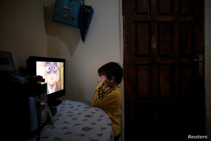 Panagiotis Argyros watches cartoons in his house at the suburb of Keratsini in Athens, Greece, March 28, 2017.