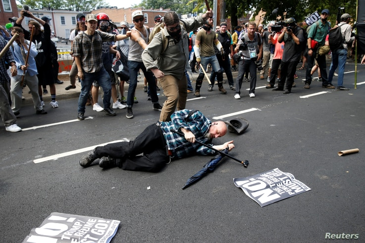 A man is down during a clash between members of white nationalist protesters and a group of counterprotesters in Charlottesville, Va., Aug. 12, 2017.