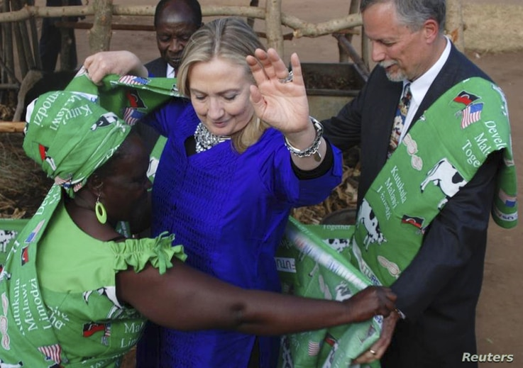 U.S Secretary of State Hillary Clinton (C) is dressed by Emmie Phiri, chairperson of the dairy farmers during her visit to Malawi August 5, 2012.