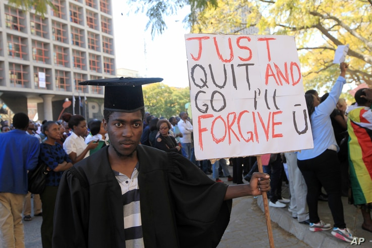 A jobless university graduate poses for a photo while holding a banner with a message directed at Zimbabwean President Robert Mugabe during protests in Harare on Aug. 3, 2016.