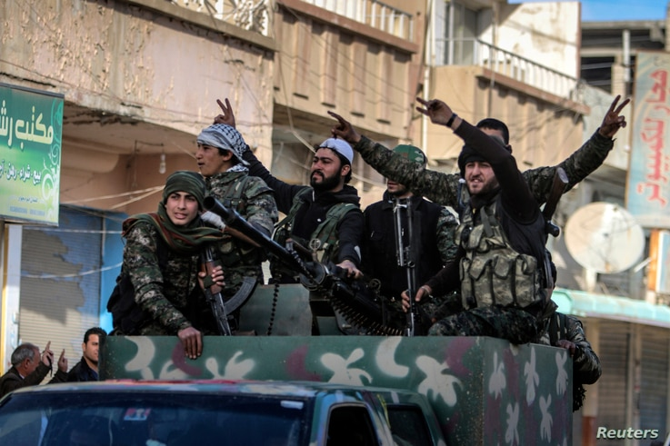 Fighters of the Kurdish People's Protection Units (YPG) carry their weapons along a street in the Syrian Kurdish city of Qamishli, in celebration after it was reported that Kurdish forces took control of the Syrian town of Tel Hamis,  Feb. 27, 2015. ...