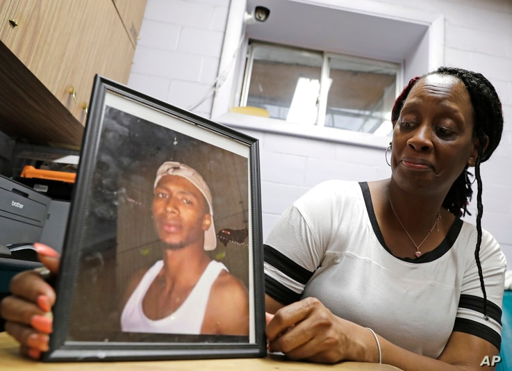 Veronica Parker holds a photo of her son, Korey B. Parker, Sr., 27, at her workplace in Chicago, Nov. 9, 2018. He was fatally shot around the corner from her house on July 4, 2012. The killing remains unsolved.