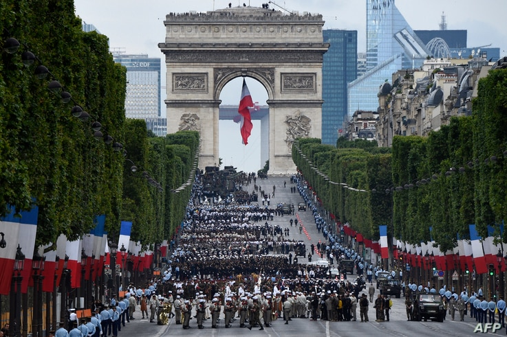 Troops wait near the Arc de Triomphe, in Paris, before taking part in the annual Bastille Day military parade on the Champs-Elysees avenue on July 14, 2016.