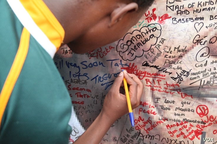 a young boy tried to squeeze his name onto a Mandela poster outside his home in Soweto, South Africa.
