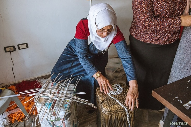 Jordanian mother of seven, Dallal Sarhan, plaits and weaves newspapers to construct a side table, at an up-cycling workshop in Irbid city, northern Jordan, May 9, 2018.
