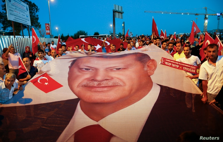 Pro-government demonstrators hold a giant Turkish national flag during a march towards the Asian side of the Bosphorus Bridge in Istanbul, Turkey, July 21, 2016.