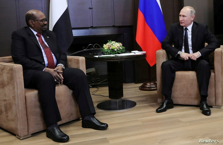 Russian President Vladimir Putin talks with Sudan's President Omar al-Bashir during their meeting in the Black Sea resort of Sochi, Russia, Nov. 23, 2017.