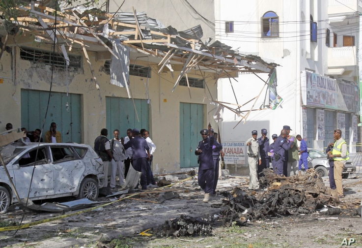 Somali soldiers stand near the wreckage after a car bomb detonated in Mogadishu, Somalia, Dec. 19, 2015.