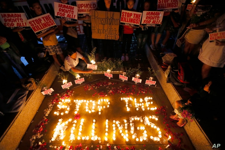 "FILE - human rights activists light candles for the victims of extra-judicial killings around the country in the wake of ""War on Drugs"" campaign by Philippine President Rodrigo Duterte in suburban Quezon city northeast of Manila, Philippines."