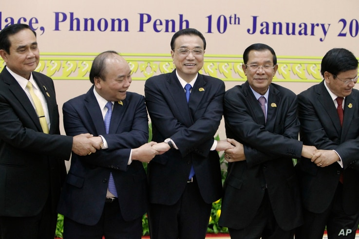 China's Premier Li Keqiang, center, shakes hands with his counterpart, Nguyen Xuan Phuc, second from left, of Vietnam, Prayuth Chan-o-cha, left, prime minister of Thailand, Hun Sen, second from right, of Cambodia, and Thongloun Sisolith, right, of La...