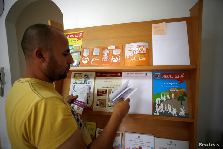 A Palestinian man check voting pamphlets in the office of the Central Elections Commission in the West Bank town of El Bireh, Aug. 17, 2016.