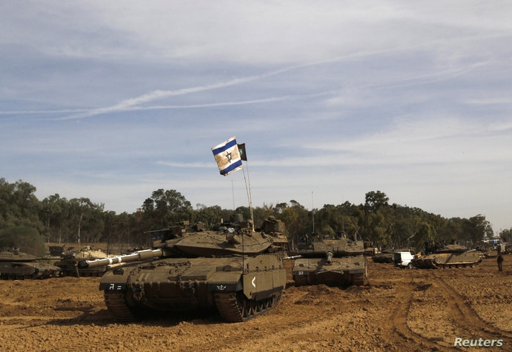 An Israeli flag is seen atop a tank at an area near the border with the Gaza Strip, November 16, 2012.