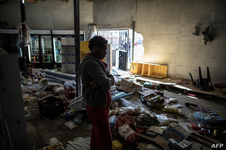 An Ethiopian owner of a looted grocery store stands in his ransacked shop, in Soweto, Johannesburg, South Africa, Aug. 29, 2018.