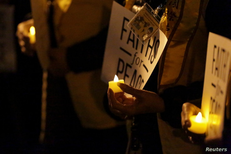 People hold signs and candles during a vigil for victims of the truck attack at Foley Square in New York, Nov. 1, 2017.