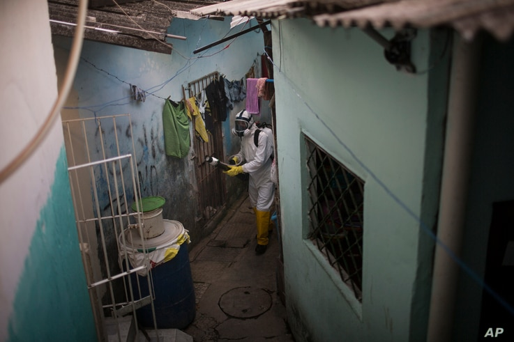 In this Jan. 26, 2016 photo, a municipal worker sprays insecticide to combat the Aedes aegypti mosquitoes that transmits the Zika virus, at the Imbiribeira neighborhood in Recife, Pernambuco state, Brazil. In the face of the spiraling public health c...