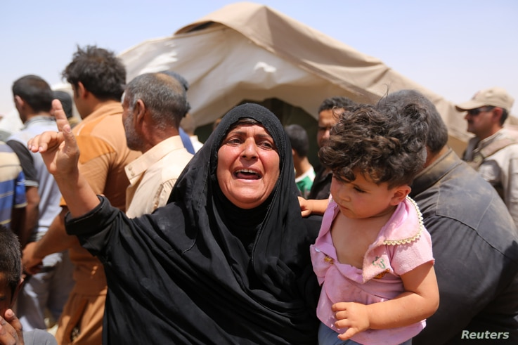A women who fled Ramadi holds a child  in a camp in the town of Amiriyat al-Fallujah, west of Baghdad, Iraq, May 22, 2015.