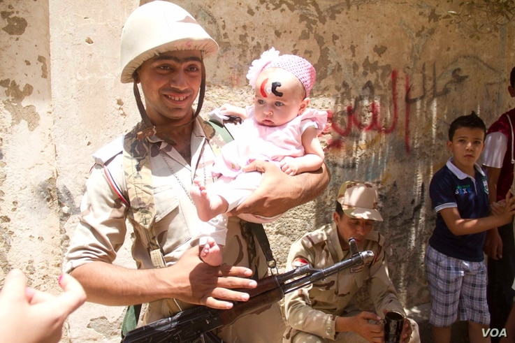 "An Egyptian soldier poses with a baby with the letters ""CC""  on her forehead standing for president Sissi in front of one of the polling stations in Bashteel in Giza, Egypt. Sissi has enjoyed support from Egypt's army, long regarded as a pillar of st..."