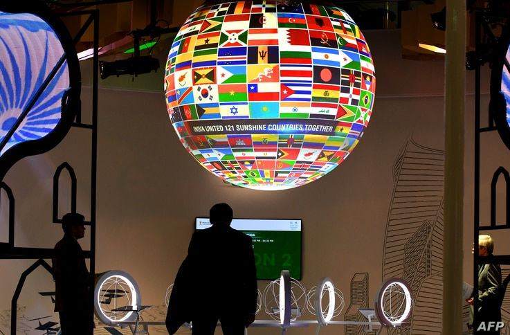 Visitors walk past a sphere featuring flags of countries of the world displayed at the pavillion of India on Nov. 8, 2017, during the COP23 U.N. Climate Change Conference in Bonn, Germany.