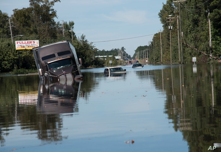 A tractor trailer truck is submerged in floodwaters caused by rain from Hurricane Matthew on Highway NC 211 near the Mayfair neighborhood in Lumberton, North Carolina, Oct. 11, 2016.