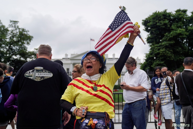 Victoria Kim, a Vietnamese Trump supporter from California, raises an American flag during a vigil outside the White House June 11, 2018, to celebrate the joint summit between U.S. President Donald Trump and North Korean leader Kim Jong Un in Singapo...