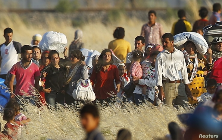 Syrian Kurds from Kobani walk to the border fences as seen from the Turkish border town of Suruc in Sanliurfa province, Turkey, June 26, 2015.