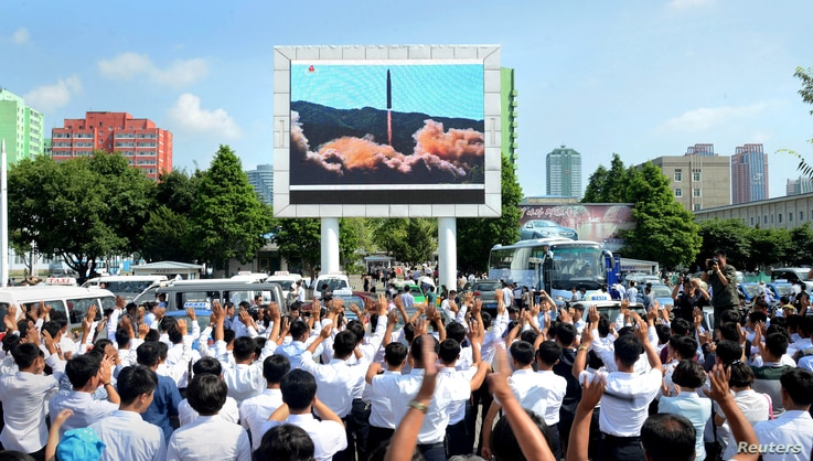 People watch a huge screen showing the test launch of intercontinental ballistic missile Hwasong-14 in this undated photo released by North Korea's Korean Central News Agency (KCNA), July 5, 2017.