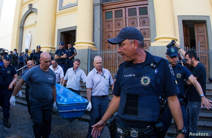 Forensic workers carry a container with a body after a shooting at Catholic cathedral in Campinas, Brazil, Dec. 11, 2018.
