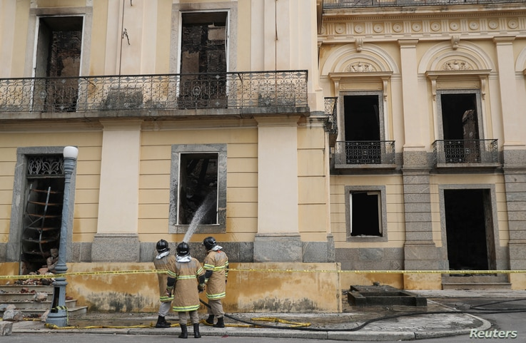 Firefighters spray water on the National Museum of Brazil after a fire in Rio de Janeiro, Brazil Sept. 4, 2018.