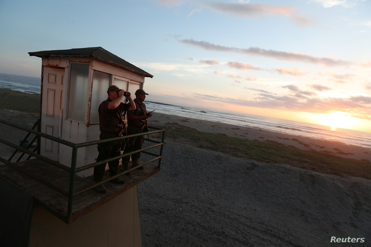 Policemen look out from a watchtower at the Chilean and Peruvian border, near Arica, Chile, Nov. 16, 2018.
