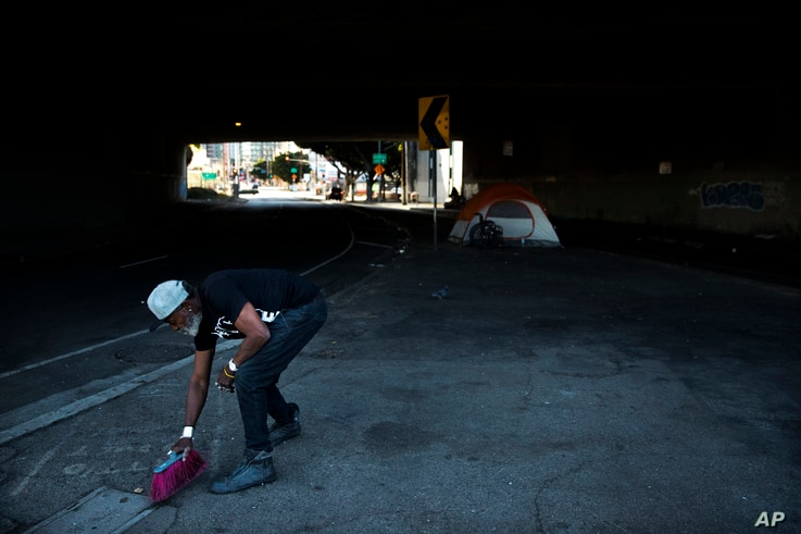 """Thurman Butler Jr., 66, who is homeless, sweeps around his tent, Dec. 1, 2017, in Los Angeles. """"A lot of people in America don't realize they might be two checks, three checks, four checks away from being homeless,"""" said Butler who became homeless af..."""